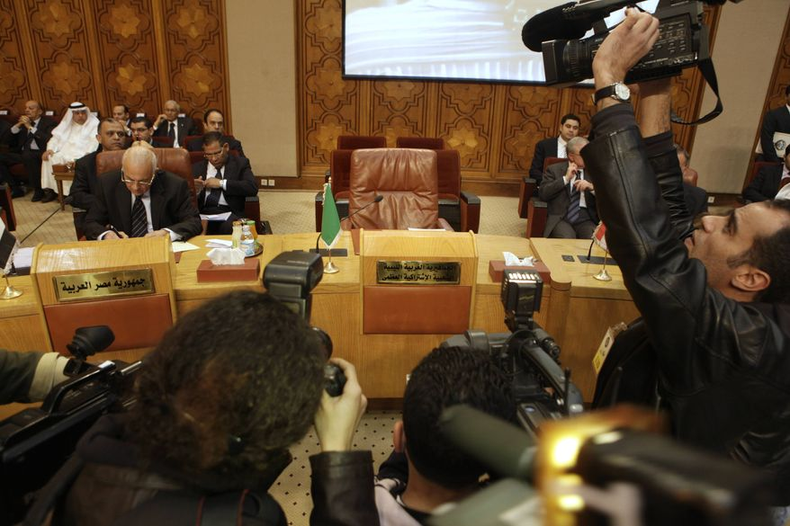 Photographers and cameramen film the Libyan empty chair during the Arab League's emergency meeting in Cairo, Egypt, on Saturday, March 12, 2011, where foreign ministers discuss the possibility of imposing no-fly zone over Libya to protect the civilian population from the Gadhafi regime's fighter jets. But the Arab League's member states are divided over how to deal with the Libyan crisis, signaling it would be a tough debate. Egyptian foreign Minister Nabil el-Arabi at left. (AP Photo/Amr Nabil)
