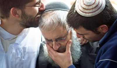 Rabbi Yehuda Ben Ishai (center), father of Ruth Fogel, and other family members mourn over the bodies of Ruth, her husband, Udi, and their three children, during their funeral. Israel said Sunday it has approved building hundreds of settler homes after the Fogels were knifed to death as they slept in a West Bank settlement over the weekend. (Associated Press)
