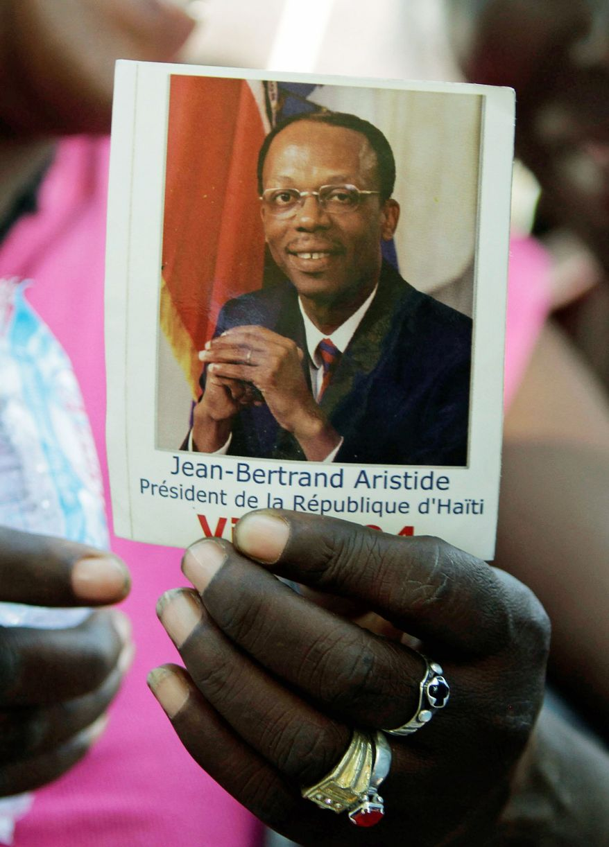 A woman holds a photo of Haiti's ousted President Jean-Bertrand Aristide during a rally in Port-au-Prince. (Associated Press)