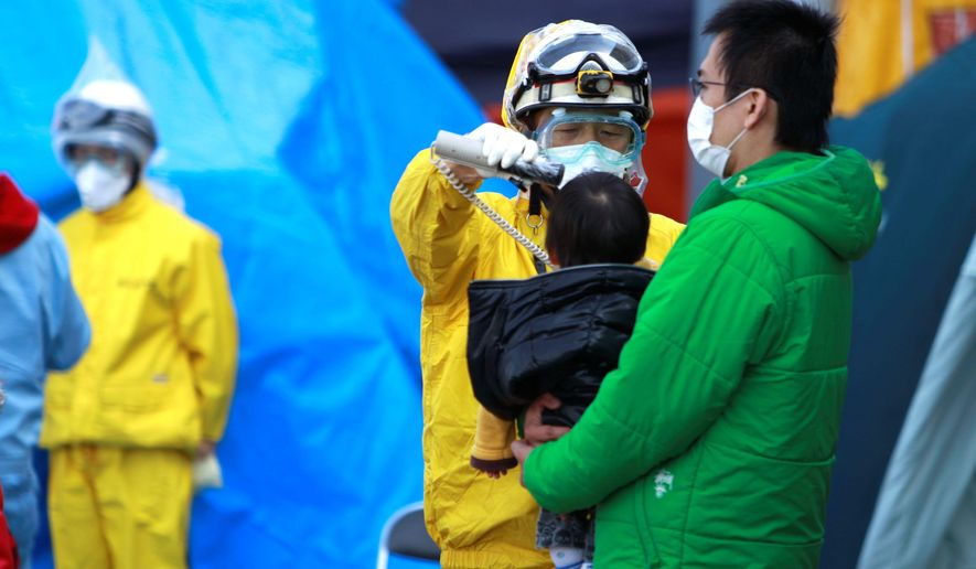 YOUNG VICTIM: A child evacuated from the area surrounding the Fukushima nuclear facilities damaged in Friday's earthquake is checked for radiation exposure with other residents on Sunday in Koriyama city in Japan's Fukushima prefecture. (Associated Press)