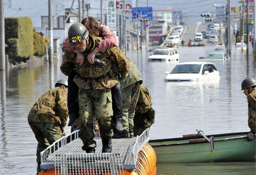 Soldiers from Japan's Self-Defense Forces rescue a tsunami victim from a flooded area in Ishinomaki in Miyagi prefecture on Sunday. The earthquake and tsunami killed at least 1,400 people, according to official estimates, and hundreds are missing. (Kyodo News via Associated Press)