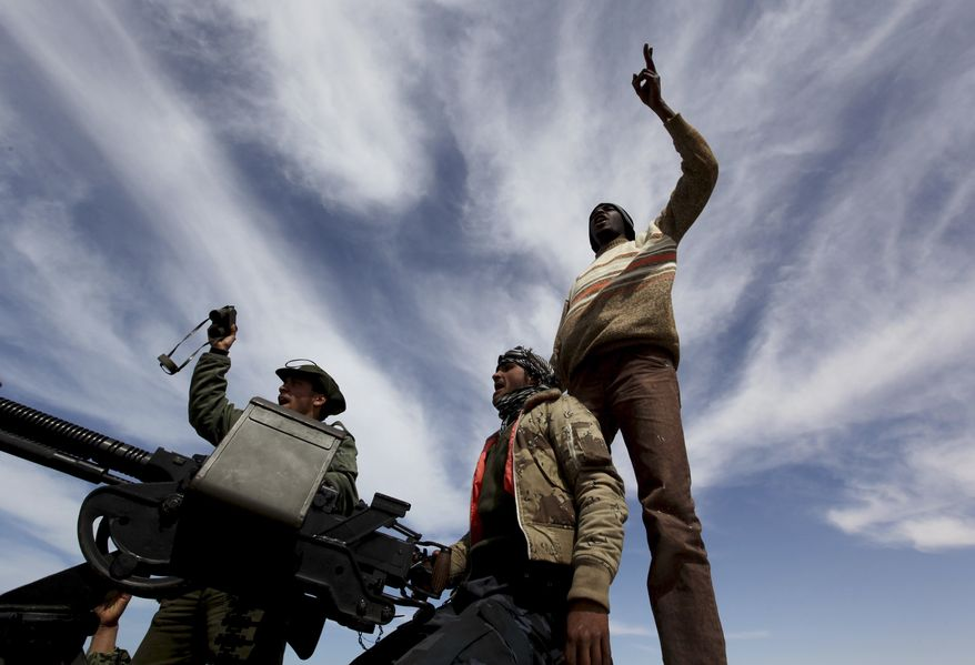 Libyan rebels opposed to Col. Moammar Gadhafi shout slogans against the leader from atop their vehicle along a desert road between the towns of Agela and Ras Lanouf in eastern Libya on Saturday, March 12, 2011. (AP Photo/Hussein Malla)