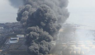 Thick smoke billows from an industrial plant in Kamaishi, Japan, on Sunday, March 13, 2011, two days after giant earchquake and tsunami struck the country's northeastern coast. (AP Photo/Kyodo News)