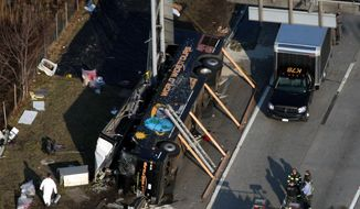 Emergency personnel respond to the bus crash on Interstate 95 in the Bronx borough of New York on Saturday, March 12, 2011, in which at least 14 people died. The bus, returning to New York from a casino in southeastern Connecticut, flipped onto its side and was sliced in half by the support pole for a large sign. (AP Photo/The Journal News, Frank Becerra Jr.)