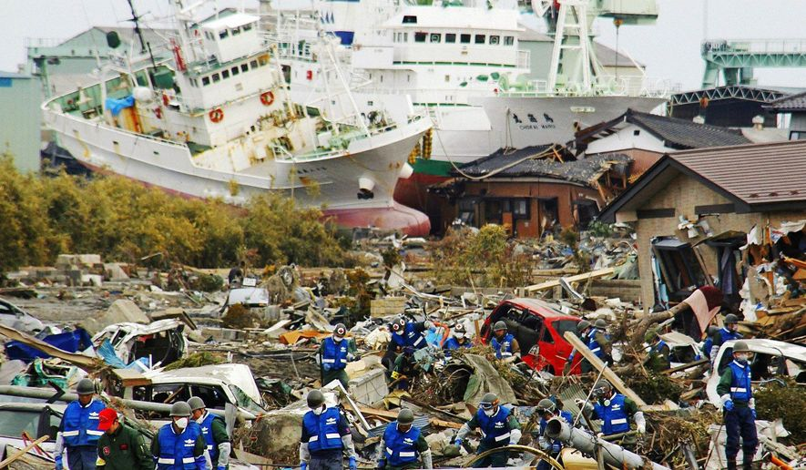 RECOVERY: Japan's Ground Defense Force searches for victims of the disaster with a backdrop of ships that were slammed into buildings. (Kyodo News via Associated Press)