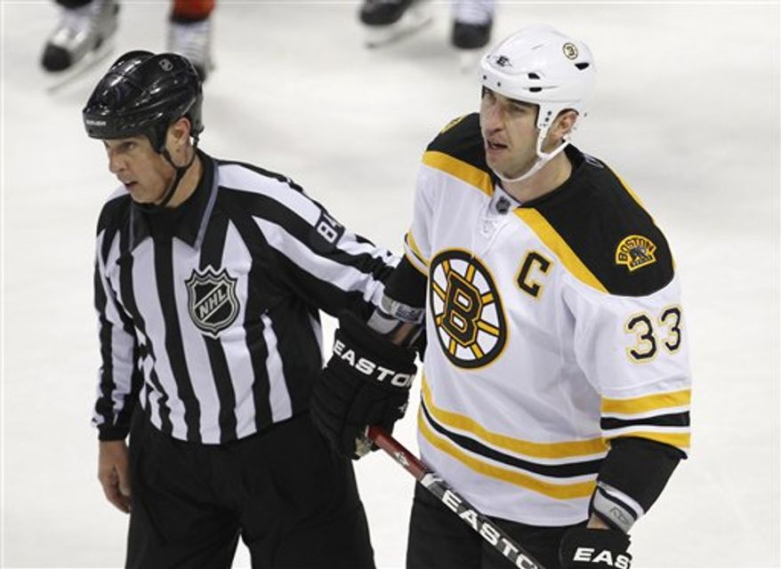 FILE - This March 8, 2011, file photo shows Boston Bruins' Zdeno Chara being escorted off the ice by an official after hitting Montreal Canadiens' Max Pacioretty during the second period NHL hockey game, in Montreal. A Quebec prosecutor wants police to investigate the on-ice hit by Boston's Zdeno Chara that sent Montreal's Max Pacioretty to the hospital with a fractured vertebra and severe concussion. (AP Photo/The Canadian Press, Paul Chiasson, File)