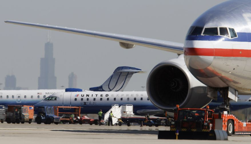 **FILE** In this photo from Oct. 5, 2010, an American Airlines jet (right) taxis past United Airlines and United Express jets at O'Hare International Airport in Chicago as the Willis Tower looms in the background. (Associated Press)