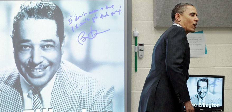 President Obama walks off after signing his name during a visit to a music classroom at Kenmore Middle School in Arlington, Va., on Monday. The students had done a presentation on jazz legend Duke Ellington. Mr. Obama called for more education spending. (Associated Press)