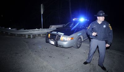 Virginia State Police Trooper S.L. Glovier blocks access to the site of a fatal shooting of two sheriff's deputies and the wounding of two others on Sunday, March 13, 2011, in Vansant, Va. (AP Photo/Jeff Gentner)