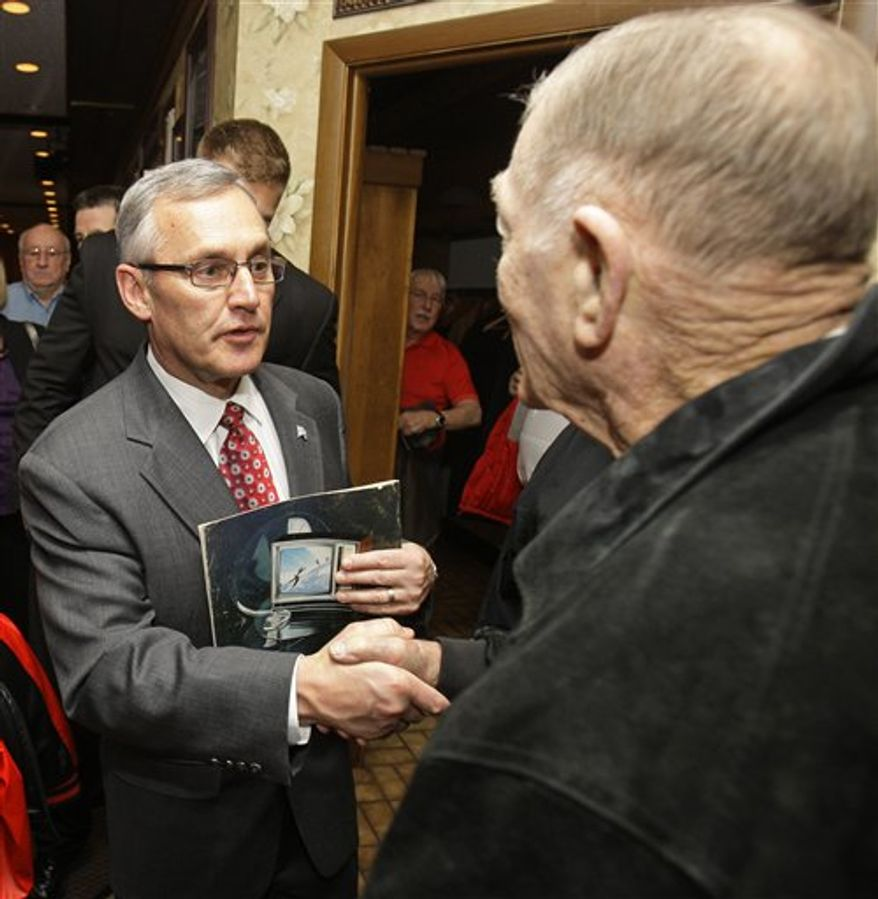 Ohio State coach Jim Tressel shakes hands with Pete Elliott, 84, after speaking at a luncheon sponsored by the Pro Football Hall of Fame Monday, March 14, 2011, in Canton, Ohio. Tressel apologized to a room full of fans during his first public speaking engagement since being suspended two games and fined for violating NCAA rules. (AP Photo)