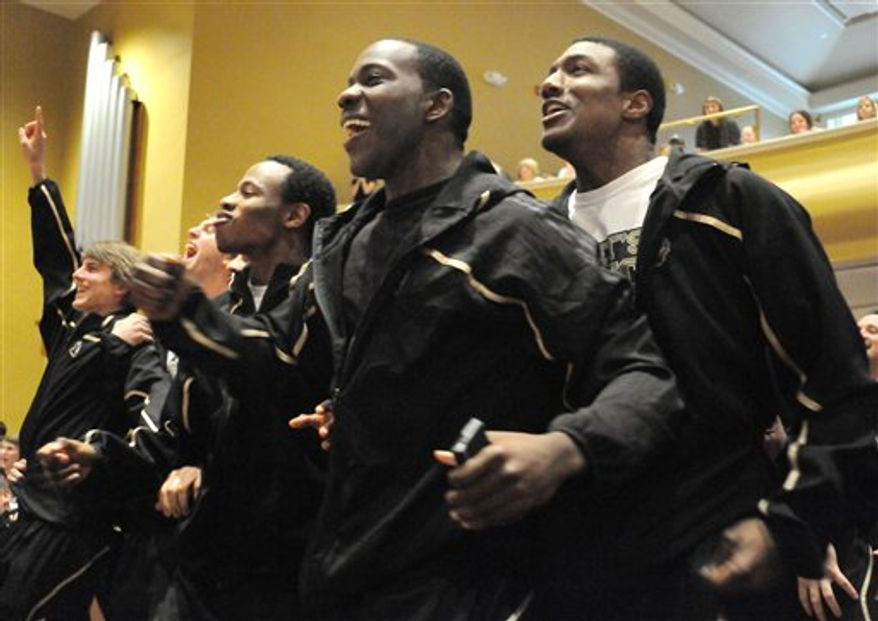 The Wofford College basketball team watches the NCAA bracket pairings for the upcoming tournament at Leonard Auditorium in Spartanburg, S.C., Sunday, March 13, 2011. Tim Johnson, center, and his teammates react to seeing they will travel to Denver to play against BYU on Thursday in the first round of the playoffs. (AP Photo/Spartanburg Herald-Journal, John Byrum)