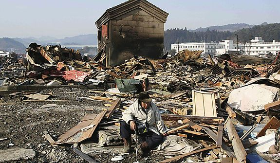 A tsunami survivor sits down in the rubble in Yamadamachi in Japan's Iwate Prefecture on Monday, March 14, 2011, three days after a powerful earthquake-triggered tsunami hit the country's east coast. (AP Photo/The Yomiuri Shimbun, Takashi Ozaki)