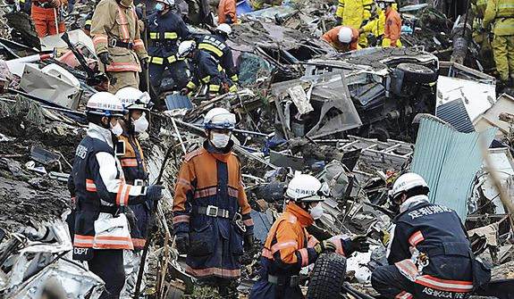 Japan Self-Defense Force members search for missing people before they use heavy machinery in Noda village in northern Japan on Monday, March 14, 2011, three days after a powerful earthquake-triggered tsunami hit the country's east coast. (AP Photo/The Yomiuri Shimbun, Yoichi Hayashi)