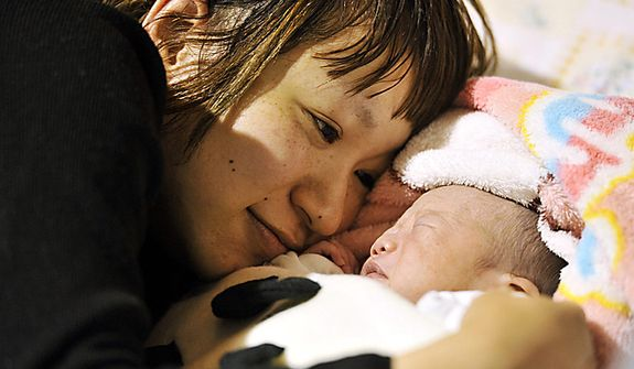 An unidentified mother watches her baby, who was born on March 2 at a shelter in Iwaki, in Japan's Fukushima Prefecture, on Monday, March 14, 2011, three days after northeastern coastal towns were devastated by an earthquake and tsunami. (AP Photo/Kyodo News)