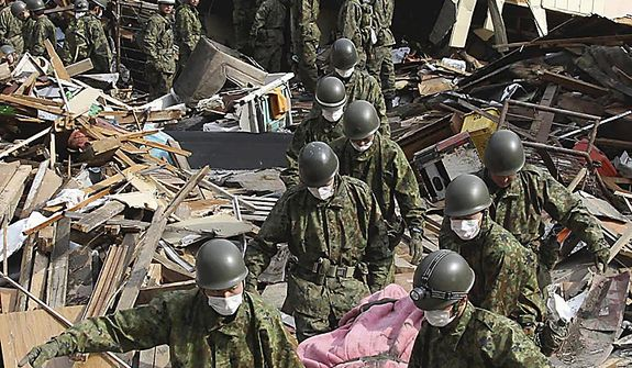 Japan Self-Defense Force members carry the body of a victim in Kamaishi, in northern Japan, on Monday, March 14, 2011, three days after a powerful earthquake-triggered tsunami hit the country's east coast. (AP Photo/The Yomiuri Shimbun, Daisuke Uragami)