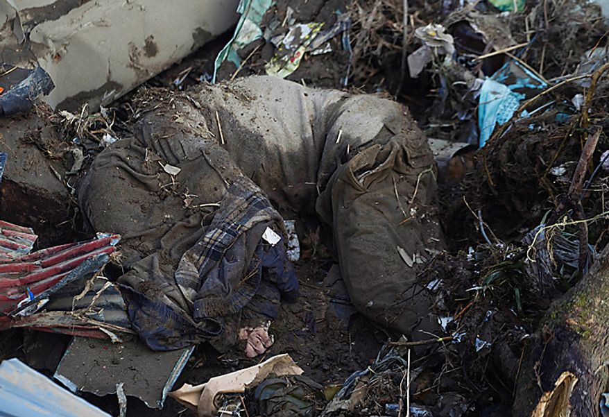 The body of a man from the village of Saito in northeastern Japan lies among the rubble on Monday, March 14, 2011. Rescue workers used chain saws and hand picks to dig out bodies in Japan's devastated coastal towns, as Asia's richest nation faced a mounting humanitarian, nuclear and economic crisis in the aftermath of a massive earthquake and tsunami that likely killed thousands. (AP Photo/David Guttenfelder)