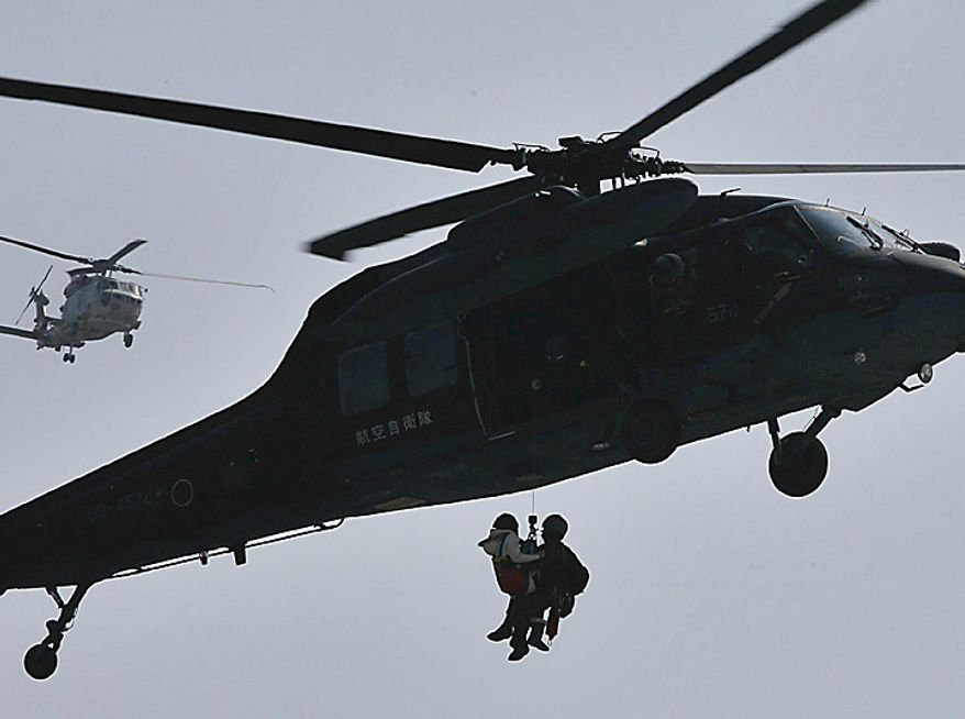 In this photo taken Sunday, March 13, 2011, a member of the Japan Air Self-Defense Force rescues a victim in Ishinomaki, in northern Japan, two days after a powerful earthquake-triggered tsunami hit the country's east coast. (AP Photo/The Yomiuri Shimbun, Makoto Kondo)