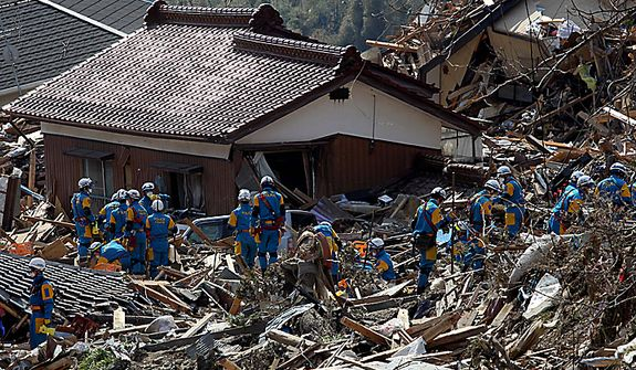 Police lead rescue teams in the search for survivors among the damaged buildings and tsunami debris in Rikuzentakada, Iwate Prefecture, Japan, on Monday, March 14, 2011. Workers battled to prevent a nuclear meltdown after a second blast rocked an atomic plant north of Tokyo, as helicopters and convoys of army trucks headed toward areas hit hardest by Japan's strongest earthquake. (Koichi Kamoshida/Bloomberg)