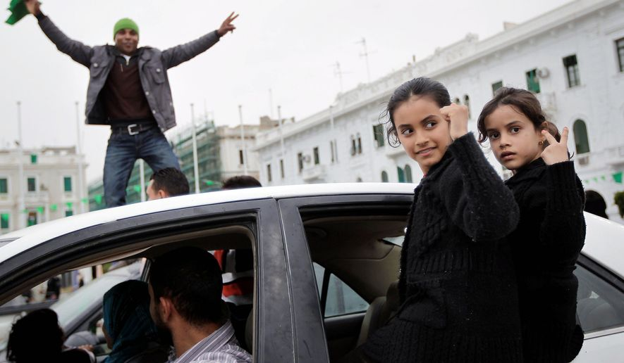 After an announcement on Libyan state television that Moammar Gadhafi's forces retook the eastern city of Adjabiya, the Libyan strongman's supporters celebrate on Green Square in Tripoli, Libya, on Tuesday. (Associated Press)