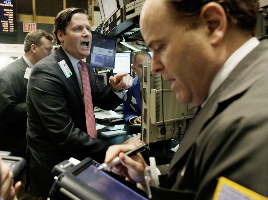Specialist Gregg Maloney (center) gives prices as he works at his post on the floor of the New York Stock Exchange on Tuesday. (Associated Press)