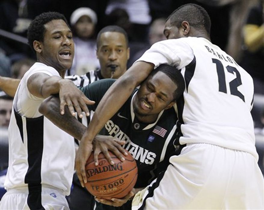 Michigan State guard Kalin Lucas gets trapped between Purdue guards Terone Johnson, left, and Kelsey Barlow (12) in the second half of an NCAA college basketball game at the Big Ten Conference tournament in Indianapolis, Friday, March 11, 2011. Michigan State beat Purdue 74-56. (AP Photo/Michael Conroy)