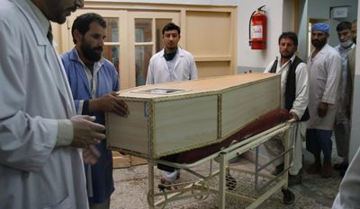 Afghans move a casket containing the body of Malang Malik, a provincial council member who killed in a blast in Mehtarlam in Laghman province, northeast of Kabul, Afghanistan, on Tuesday, March 15, 2011. An Afghan government spokesman said the council member was killed while walking near his home. (AP Photo/Rahmat Gul)