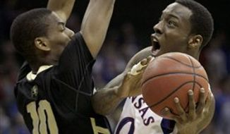 Kansas forward Thomas Robinson (0) is pressured by Colorado guard Alec Burks (10) while putting up a shot during the second half of an NCAA college basketball game in the semifinals of the Big 12 men's basketball tournament on Friday, March 11, 2011, in Kansas City, Mo. (AP Photo/Charlie Riedel)