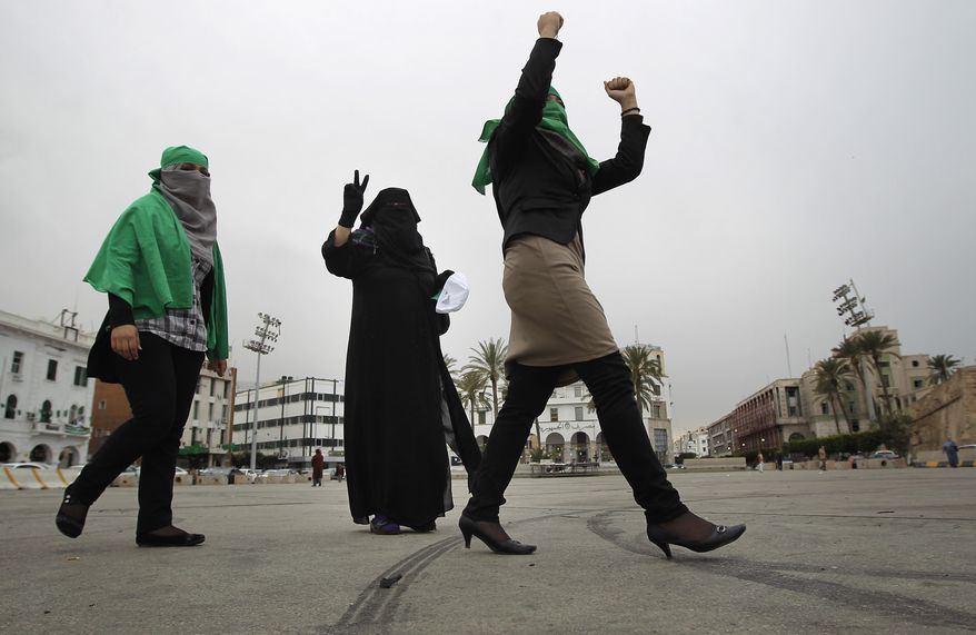 Three supporters of Col. Moammar Gadhafi celebrate on Green Square in Tripoli, Libya, on Tuesday, March 15, 2011, after an announcement on state TV that pro-Gadhafi troops had taken the eastern city of Ajdabiya.  (AP Photo/Jerome Delay)