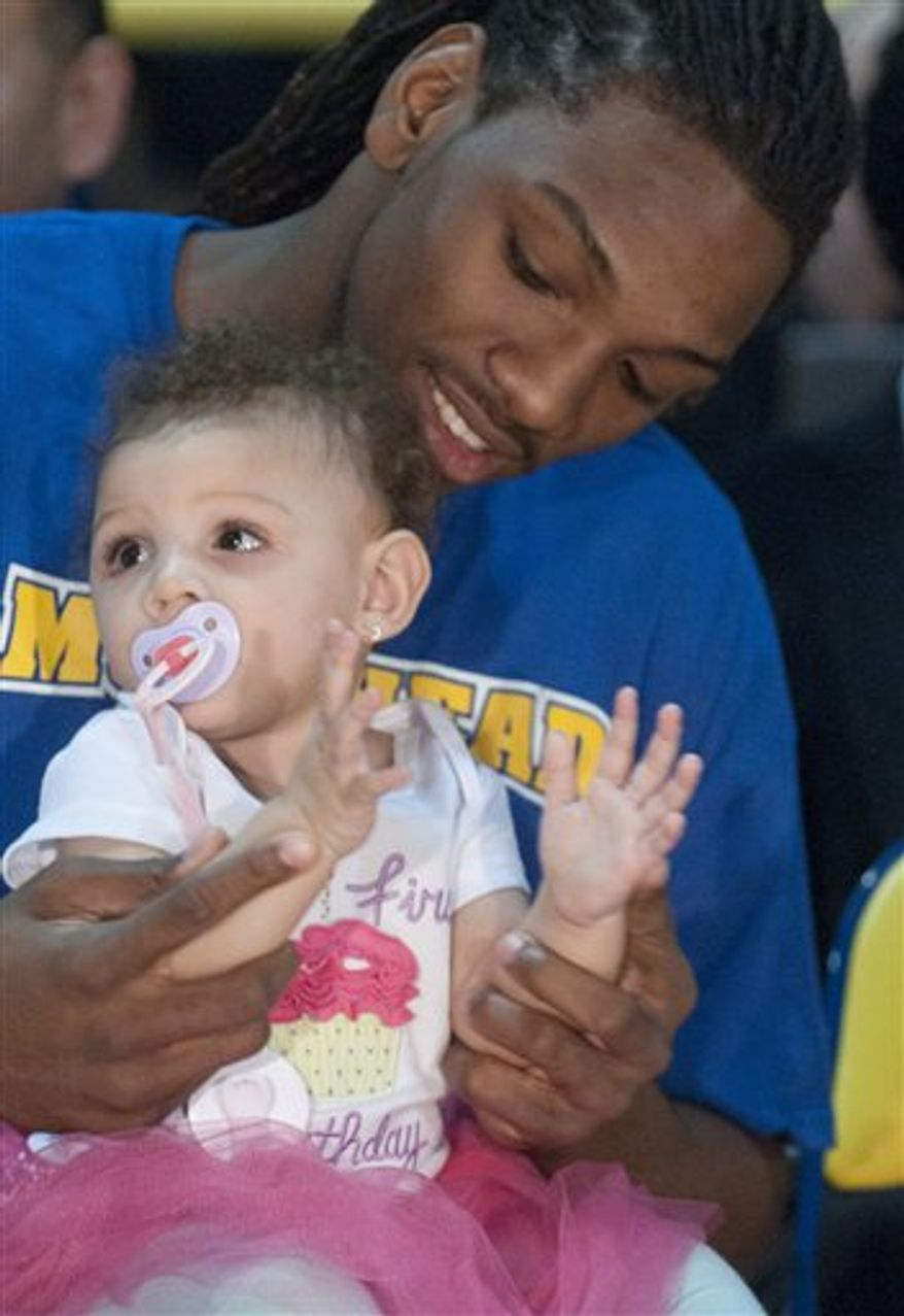 Morehead State forward Kenneth Faried plays with his year-old daughter, Kyra, Sunday, March 13, 2011, in Morehead, Ky., while waiting for the NCAA college basketball tournament selection show. Morehead State is scheduled to face Louisville on Thursday. (AP Photo/The Independent/John Flavell)