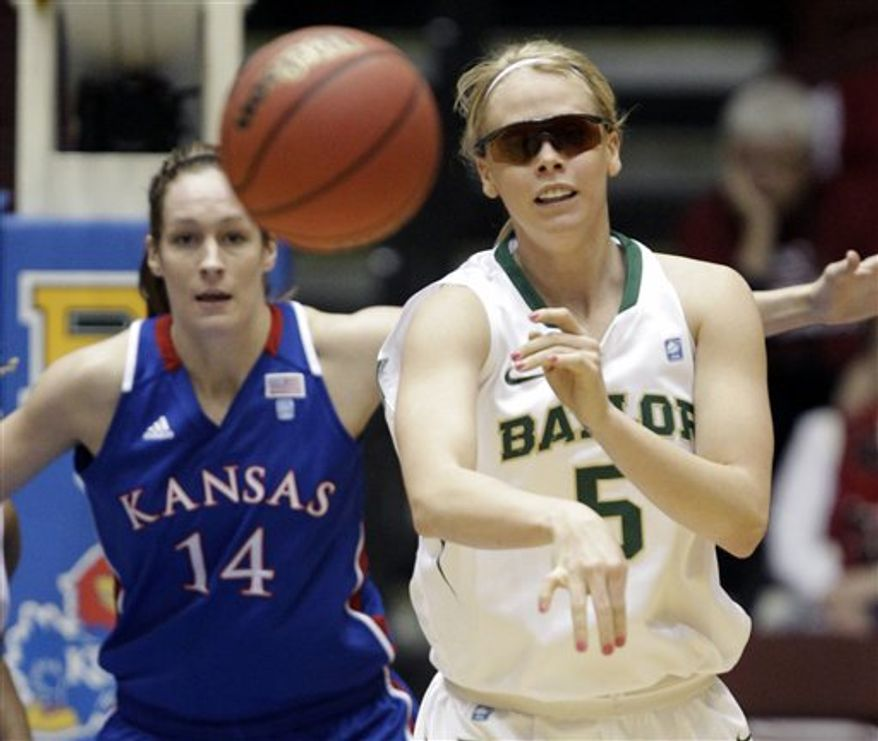FILE - In this March 9, 2011 file photo, Baylor's Melissa Jones passes the ball as Kansas' Krysten Boogaard (14) looks on during the first half of an NCAA college basketball game at the Big 12 Conference women's tournament in Kansas City, Mo. Jones, the gritty player known as `MJ' and already admired for her hard-nosed play, has been playing without vision in one eye since hitting her head on the floor going for a loose ball two weeks ago. (AP Photo/Jeff Roberson, File)