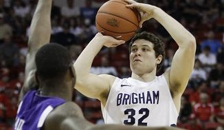 FILE - This March 10, 2011, file photo shows BYU's Jimmer Fredette putting up a three point shot over TCU's J.R. Cadot during the first half of an NCAA college basketball game in the second round of the Mountain West Conference tournament, in Las Vegas. Instead of only defending the basket and the lane, teams have to also worry about defending the 3s.  (AP Photo/Julie Jacobson, File)