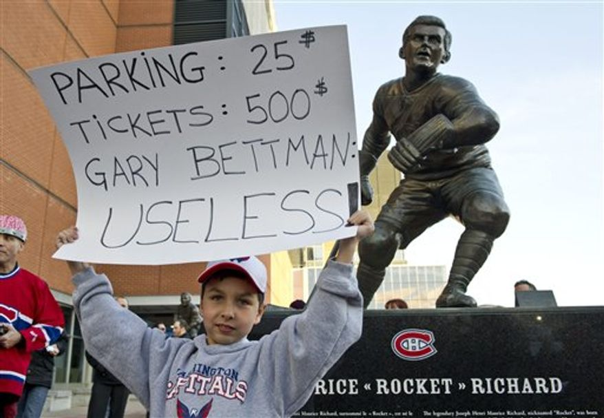 Anthony Semerano, 10, from Montreal, holds up a placard in front of a statue of hockey legend Maurice Richard during a protest against violence in hockey and a call for tougher sanctions from the NHL for hits to the head, Tuesday, March 15, 2011 in Montreal. (AP Photo/The Canadian Press, Paul Chiasson)