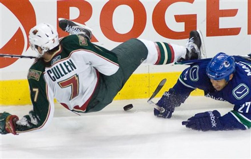 Vancouver Canucks left wing Jeff Tambellini (10) collides with Minnesota Wild right wing Antti Miettinen (20) during the third period of an NHL hockey game Monday, March 14, 2011, in Vancouver, British Columbia. Vancouver won 4-2. (AP Photo/The Canadian Press, Geoff Howe)