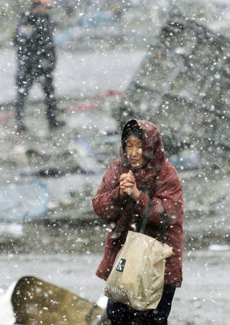 HOMELESS: A woman walks around the devastated area in snowy and cold Ofunato in northern Japan where her home used to be before the earthquake and tsunami on Wednesday. Emperor Akihito appeared on TV across Japan in a prerecorded message that lasted about six minutes. (Associated Press/Kyodo News)