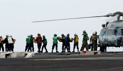 Sailors move food and water onto an HH-60H Sea Hawk on the flight deck of the aircraft carrier USS Ronald Reagan on Tuesday off the coastline of Japan in the western Pacific Ocean. (Associated Press via U.S. Navy)