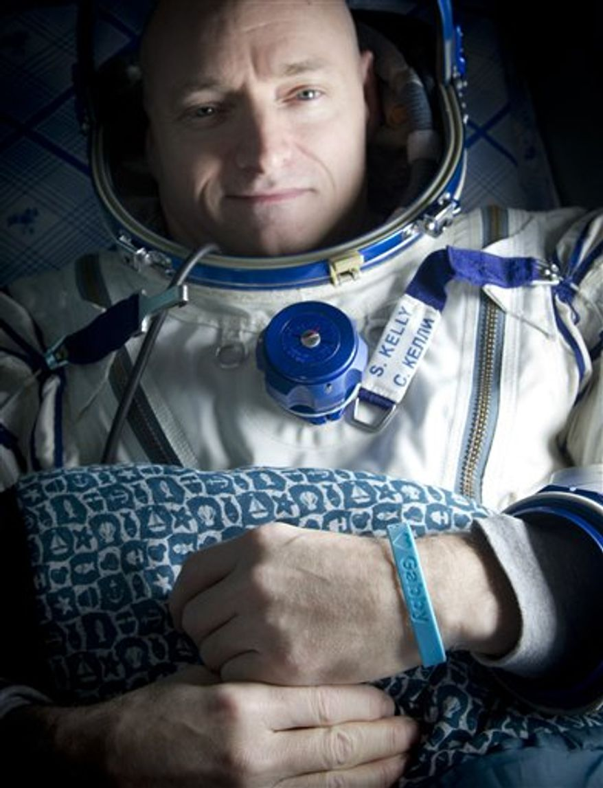 """In a photo provided by NASA, Expedition 26 Commander Scott Kelly wears a blue wrist band that has a peace symbol, a heart and the word """"Gabby"""" to show his love of his sister-in-law, U.S. Rep. Gabrielle Giffords, as he rest onboard a Russian Search and Rescue helicopter shortly after he and fellow crew members Oleg Skripochka and Alexander Kaleri landed in their Soyuz TMA-01M capsule near the town of Arkalyk, Kazakhstan on Wednesday, March 16, 2011.  NASA astronaut Kelly, and Russian cosmonauts Skripochka and Kaleri are returning from almost six months onboard the International Space Station where they served as members of the Expedition 25 and 26 crews. (AP Photo/NASA, Bill Ingalls)"""