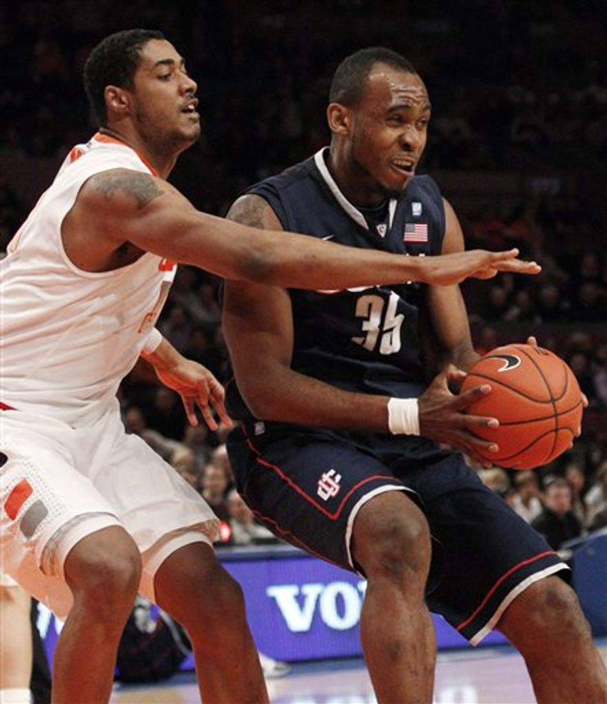 Connecticut's Charles Okwandu, right, drives past Syracuse's Fab Melo during the first half of an NCAA college basketball game at the Big East Championship Friday, March 11, 2011, in New York. (AP Photo/Frank Franklin II)
