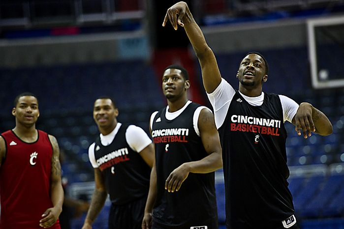 At right, University of Cincinnati sophomore guard Cashmere Wright follows through on a shot during open practice, at the Verizon Center, in Washington, D.C., Wednesday, March 16, 2011. (Drew Angerer/The Washington Times)