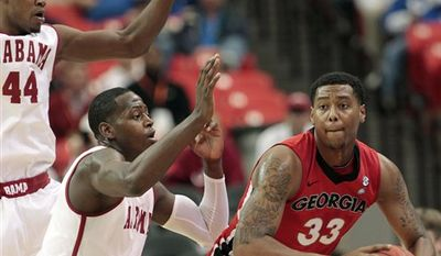 Georgia forward Trey Thompkins (33) looks to pass as Alabama forward JaMychal Green (1) and Alabama forward Chris Hines (44) defend during the first half of an NCAA college basketball game at the Southeastern Conference tournament, Friday, March 11, 2011, in Atlanta. (AP Photo/Dave Martin)