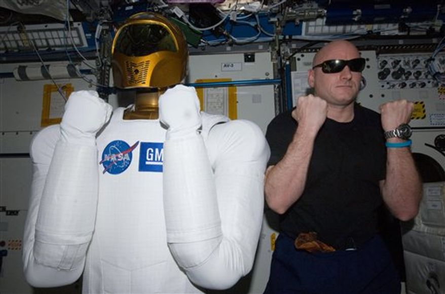 In this March 15, 2011 photo provided by NASA, astronaut Scott Kelly, Expedition 26 commander, right, poses with Robonaut 2, the dexterous humanoid astronaut helper, in the Destiny laboratory of the International Space Station. (AP Photo/NASA)