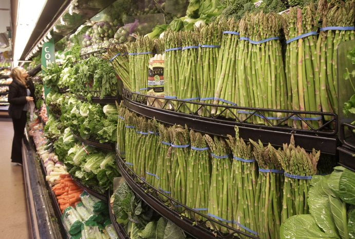 ** FILE ** A customer looks at fresh vegetables at a Kroger Co. supermarket in Cincinnati on Monday, March 1, 2011. (AP Photo/Al Behrman)