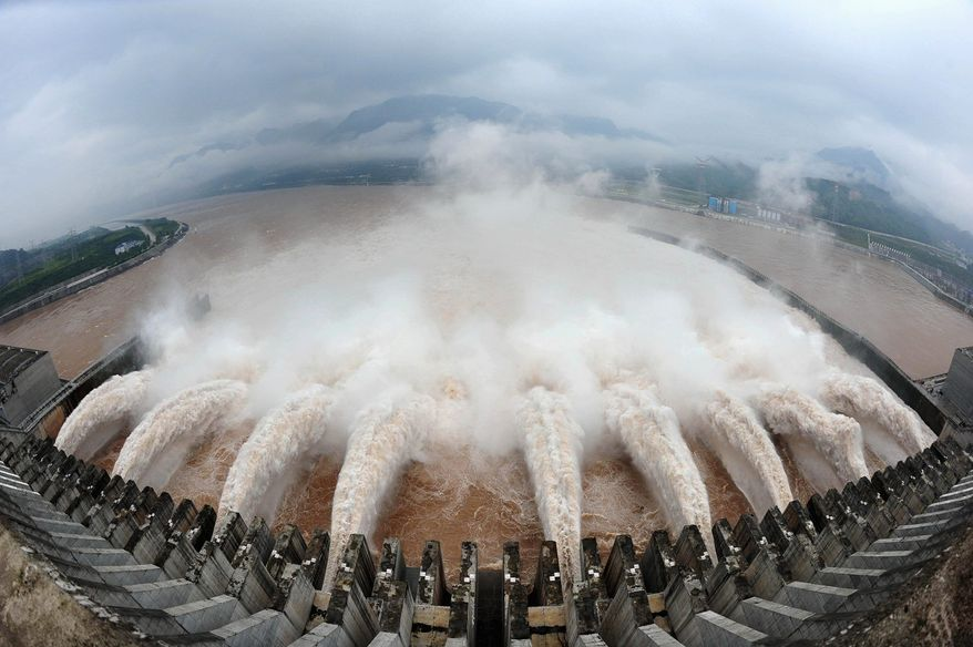 Flood water is released from the Three Gorges Dam's floodgates in Yichang, China, after heavy rains last summer. Critical infrastructure controlled by computers, including dams, pipelines and factories, are more vulnerable to cyber-attacks in China than in other countries, security specialists say. Three Gorges is the largest dam in the world. (Associated Press)