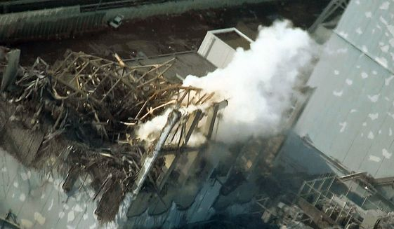 DANGER: Thick smoke billows from the No. 3 unit of the Fukushima Dai-ichi nuclear power plant in Japan. A nearly completed new power line could restore cooling systems to the tsunami-damaged structure, its operator said Thursday. (Associated Press)