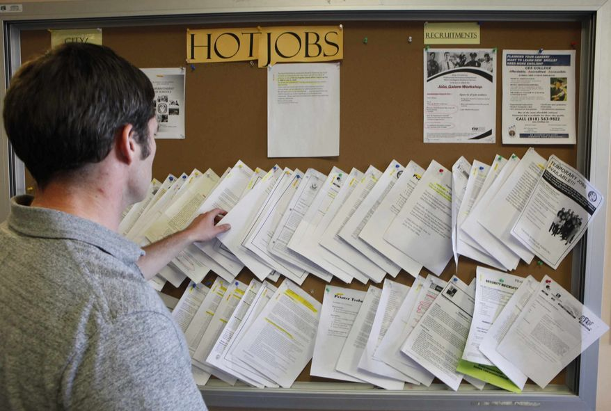 In this photo taken on on Thursday , Feb. 3, 2011, an unidentified job seeker looks for an auto mechanic job opportunity at the Verdugo Job Center in Glendale, Calif. Fewer laid-off workers applied for unemployment benefits, marking third drop in four weeks. (AP Photo/Damian Dovarganes)
