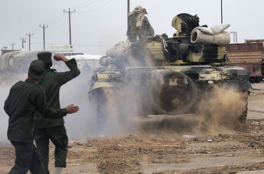 Libyan soldiers loyal to Col. Moammar Gadhafi are seen on the western entrance of the city of Ajdabiya, Libya, on Wednesday, March 16, 2011. (AP Photo/Jerome Delay)