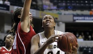 In this March 3, 2011, photo, Purdue forward Drey Mingo, center, shoots between Indiana guards Whitney Lindsay, left, and Jori Davis during NCAA college basketball game in the Big Ten tournament in Indianapolis. Four months ago, Mingo lay unconscious on her apartment floor with an illness that gave her a 50 percent chance of survival. On Sunday, the Purdue forward will lead her team into the NCAA tournament. (AP Photo)