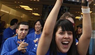 FILE - In this March 11, 2011 file photo, Apple employees cheer as the iPad 2 goes on sale at The Grove Apple store in Los Angeles. Analysts from IHS iSuppli said Friday, March 18, 2011, last week's earthquake in Japan could cause shortages of the iPad 2. (AP Photo/Damian Dovarganes, file)