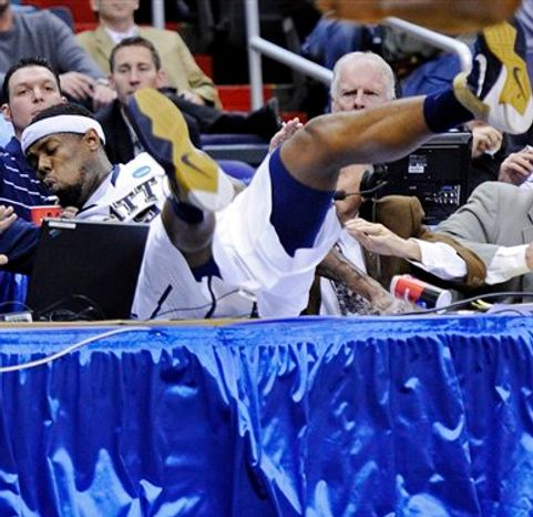Pittsburgh forward Nasir Robinson crashes into the courtside tables during the second half of a Southeast regional second round NCAA tournament college basketball game against UNC-Asheville, Thursday, March 17, 2011, at the Verizon Center in Washington. (AP Photo/Nick Wass)