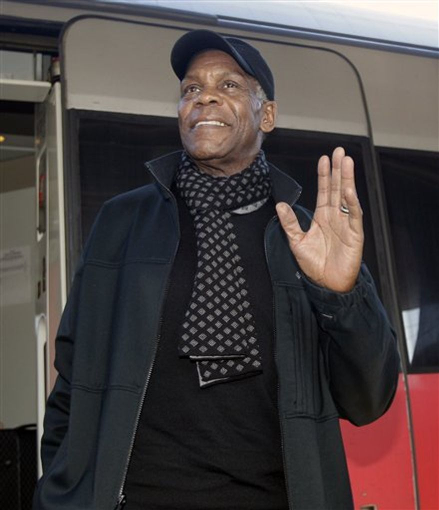 "FILE - In this photo taken Friday, Feb. 4, 2011 file photo US actor Danny Glover gestures as he arrives at Rome's main train station. The lawyer of Haiti's Jean-Bertrand Aristide says actor Danny Glover has arrived in South Africa to escort the exiled former president home. Miami lawyer Ira Kurzban flew to Johannesburg Wednesday on the same mission amid unexplained delays as the United States called for Aristide to put off his departure until Sunday's disputed presidential runoff in his homeland. Kurzban says the star of the ""Lethal Weapon"" action movies arrived Thursday, March 17, 2011. (AP Photo/Pier Paolo Cito, File)"