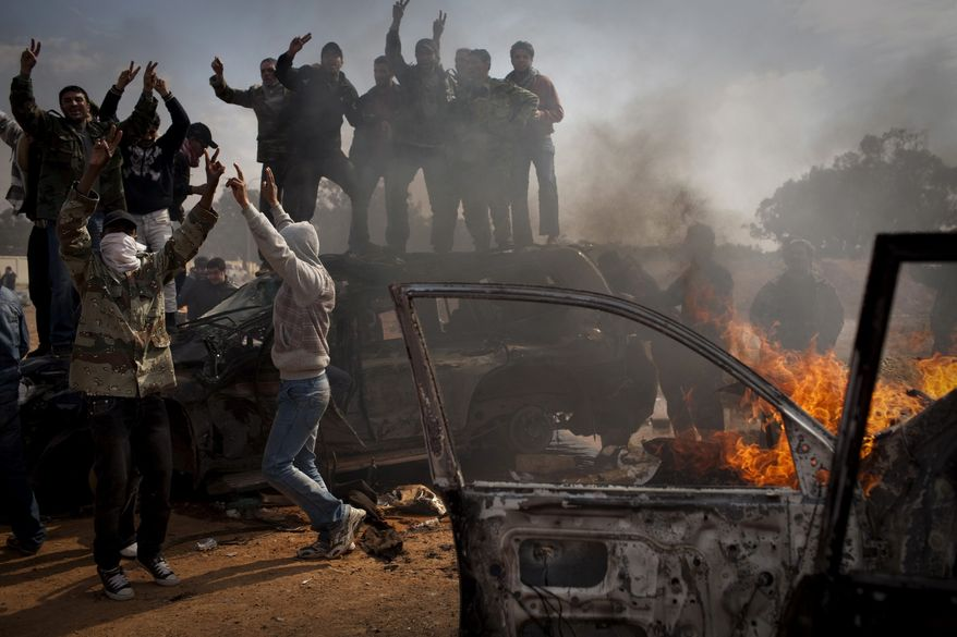 Libyan rebels celebrate next to burning cars after Libyan leader Moammar Gadhafi's forces where pushed back from Benghazi, eastern Libya, Saturday, March 19, 2011. Explosions shook the Libyan city of Benghazi early on Saturday while a fighter jet was heard flying overhead, and residents said the eastern rebel stronghold was under attack from Muammar Gaddafi's forces. (AP Photo/Anja Niedringhaus)